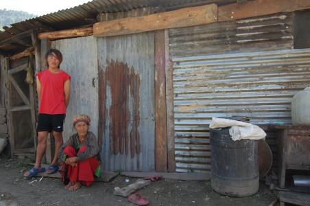 """Miju und Tsewang vor ihrem derzeitigen Haus, das sie aus verwertbarem Wellblech, Holz und den neuen Wellblechplatten gebaut haben. """"Für den Winter reicht das nicht"""", sagt Tsewang."""